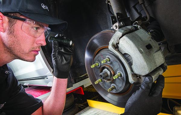 Man checking brakes on vehicle