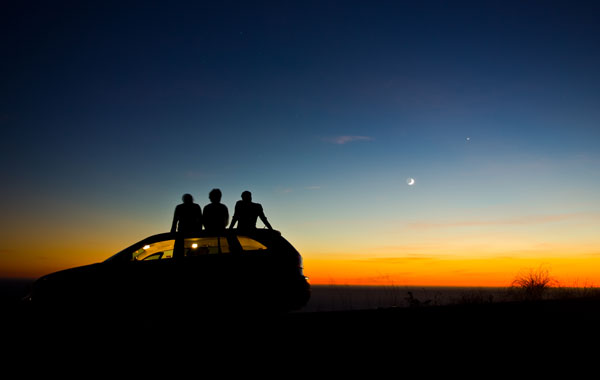 Family on car looking at night sky