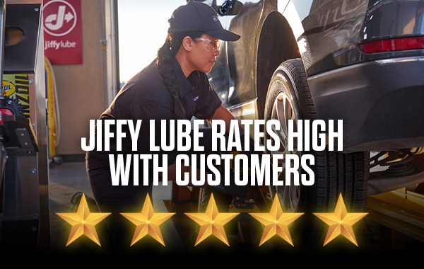 Jiffy Lube technician working on suspended car with bottom text saying Jiffy Lube Rates High With Customers