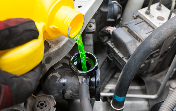 Closeup of coolant being dripped into vehicle coolant tank
