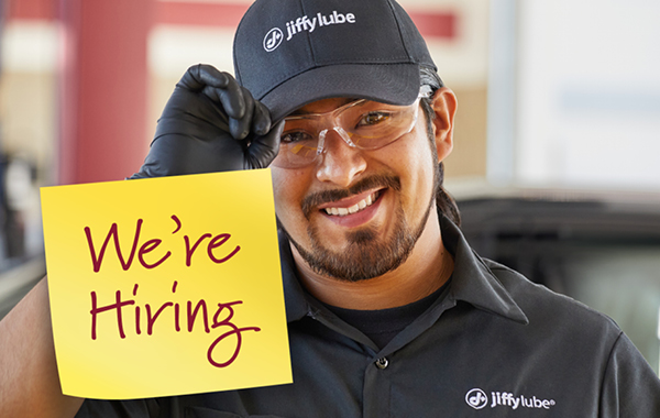 male jiffy lube employee with sign that says we're hiring
